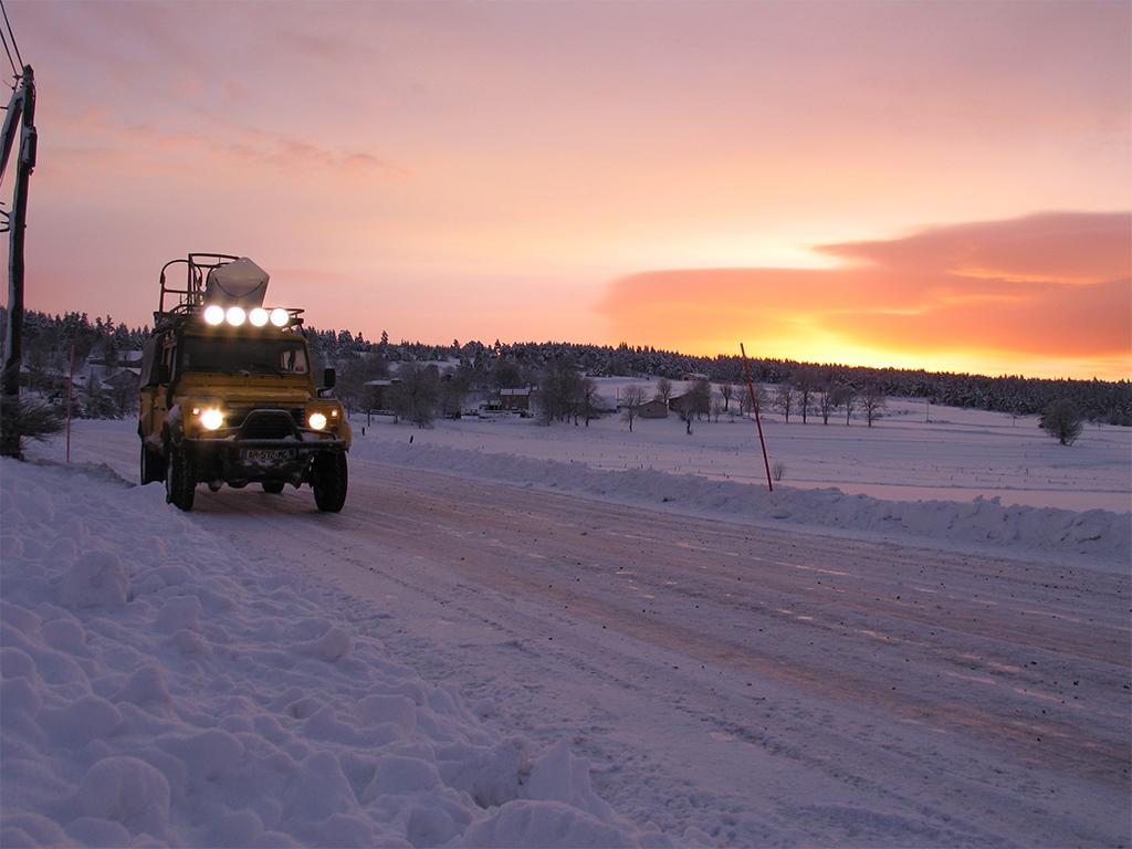 Au coucher du soleil, le ciel orangé contraste avec la blancheur de la neige